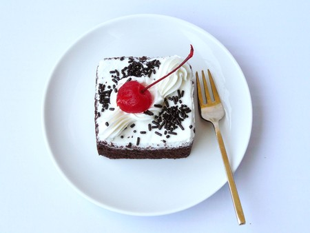Delicious mini chiffon - chocolate cake, The chocolate - chiffon cake decorated with milk cream and red cherry in a white plate with brass fork. Close up top view isolated on white background.