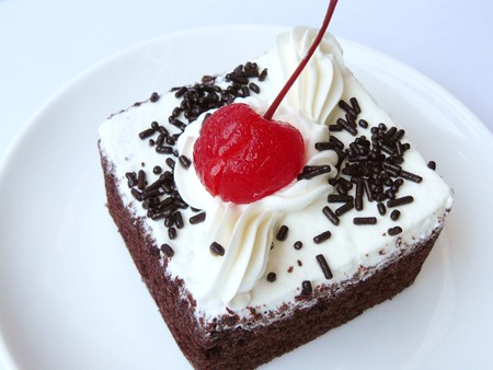 Delicious mini chiffon - chocolate cake, The chocolate - chiffon cake decorated with milk cream and red cherry in a white plate. Close up side view isolated on white background.