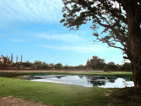 Landscape of distant view the ruin of Sukhothai kingdom at side of big pond and beautiful blue sky at Sukhothai Historical Park. Sukhothai province,