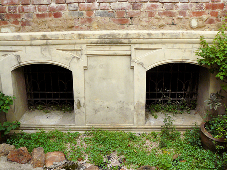 Twin window of basement and red brick stone wall above it, the vintage windows of antique neo-classic abandoned house.