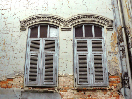 Old wooden Neo-Classic window and cracked of old cement wall seeing red brick stone beneath it, the vintage windows of antique abandoned house.