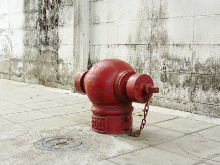 Thai red fire hydrant or red street water valve, is are emergency water supply on a white concrete footpath in front of a dirty wall with stain. Stock Photo