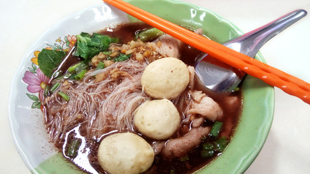 Delicious Asia - Asian eating: Thai-Chinese food. The rice vermicelli in thicken soup with topping pork ball, slice pork and green vegetable ( water convolvulus and etc. ) isolate on white background. Stock Photo