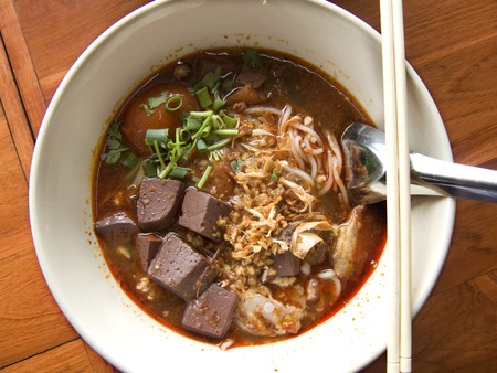 Delicious Asia - Asian eating: Thai traditional food. Rice noodles with spicy pork sauce soup. Thai name is Kanom Jeen Nam Ngeaw. Close up top view on wooden table background. Stock Photo