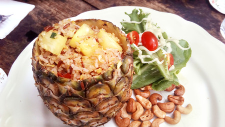 Delicious Asia - Asian eating Thai food. Pineapple fried rice stir with curry powder in pineapple shell served with salad, cashew nuts and Thai fish spicy sauce, Close up top view in a white plate.
