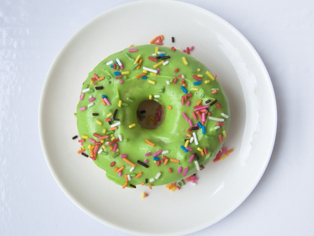 Close up top view of Green Donut decorated with colorful sugar topping on a white plate isolated on white background. Stock Photo
