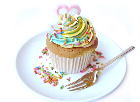 Love heart rainbow cupcake. Vanilla cake in paper cup decorated with colorful rainbow cream and sugar color on a white plate with fork isolated on white background.