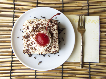 Close up front view of mini Coffee black forest cake, Delicious the chocolate-rum cake decorated coffee with milk cream and red cherry on a white plate and fork on Rattan palm mat background. Stock Photo