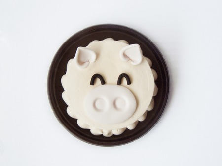 Delicious sweet cute piglet vanilla cream cake. The vanilla cake decorated with cream sugar color in a shape of cartoon style. Close up top view on a brow plate, isolated on background.