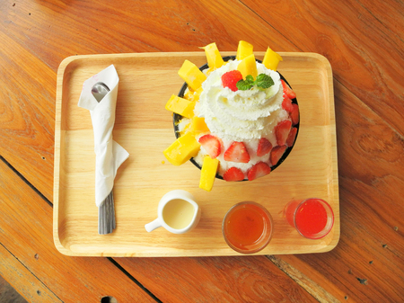Delicious Asia-Asian eating food, Bing su: Korean shaved milk ice dessert with strawberry and mango sweet toppings and fresh fruit, strawberry, mango in a big bowl. Close up top view on a wooden table