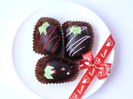 Trio Chocolate ball decorated with colorful sugar topping seem like strawberry in paper cup and red love ribbon in a white plate isolated on white background.