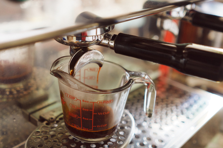 Barista cured coffee. Distill in the coffee machine to get a cup of tea, where the coffee machine has constant temperature control. vintage tone. Stock Photo
