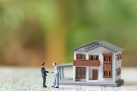 Miniature 2 people businessmen Shake hands with A model house model .as background  business concept and real estate concept with copy space. Stok Fotoğraf