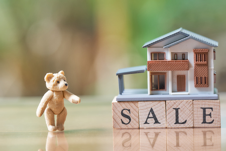 A model house model and Teddy Bear is placed on wood.  word sale as background business concept and real estate concept with copy space.