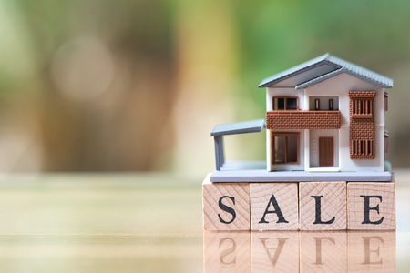 A model house model is placed on wood word sale . as background property real estate concept with copy space for your text or  design. Stock Photo