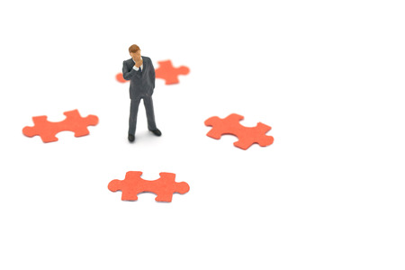 Miniature people businessmen standing with jigsaw puzzles analyze the business process, find the problem or component to succeed.using as background business concept with copy space. Stock Photo