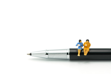 Miniature people Sit on the pens, exchange ideas, discuss problems using as background business concept and finance concept with copy space  for your text or  design.