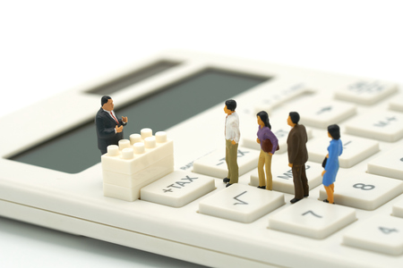 Miniature people Pay queue Annual income (TAX) for the year on calculator. using as background business concept and finance concept with copy space for your text or design. Stock Photo