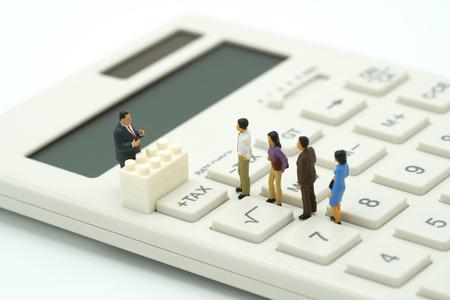 Personnes miniatures Payer la file d'attente Revenu annuel (TAXE) pour l'année sur la calculatrice. en utilisant comme concept d'entreprise d'arrière-plan et concept financier avec un espace de copie pour votre texte ou votre conception.