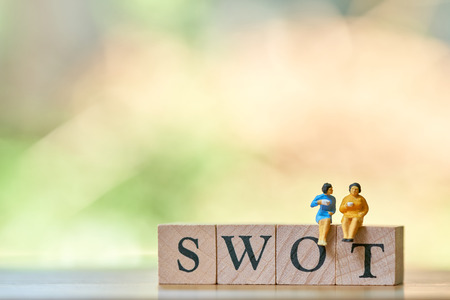 Miniature 2 people sitting on wood word SWOT using as background business concept and Strategy concept with copy space for your text or design.