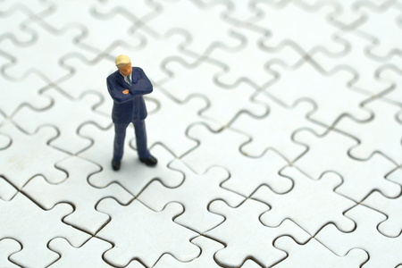 Miniature people businessmen standing on white Jigsaw. using as background business concept and finance concept with copy space  for your text or  design.