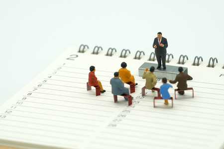 Miniature people sitting on red staples placed on a Book Rankings (list). meeting or Discussion using as background business concept with copy space and white space for your text or  design. Stok Fotoğraf