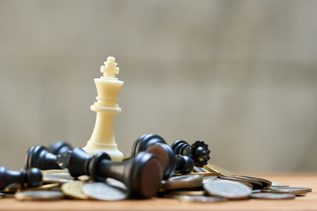 A King Chess is placed on a pile of coins.using as background business concept and Strategy concept with copy space for your text or design. Stok Fotoğraf