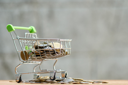 Saving money concept of collecting coins (Thai money) in a Shopping Cart on nature background.  as background business concept and Saving concept with  copy space for your text or design.