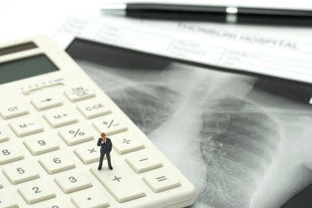 Miniature people businessmen standing on white calculator with Lung x-ray .using as background Healthcare concept and Medical concept with copy space.