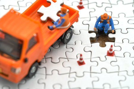Miniature people Construction worker on white Jigsaw. using as background business concept and finance concept with copy space  for your text or  design. Stok Fotoğraf
