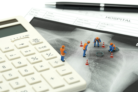 Miniature people Construction worker on white calculator with Lung x-ray .using as background Healthcare concept and Medical concept with copy space and white space.