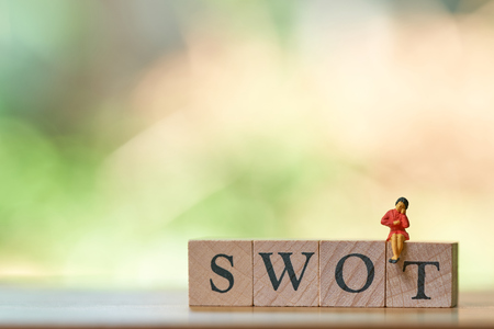Miniature people sitting on wood word SWOT using as background business concept and Strategy concept with copy space for your text or design. Stok Fotoğraf