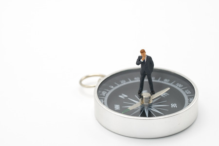 Miniature people businessmen analyze standing on compass as background strategy concept and Business concept with copy space and white space. Stok Fotoğraf