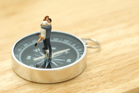 Couple Miniature 2 people standing on a  compass Communicate the direction of the couple. using as background Valentine concept with copy spaces for you Stok Fotoğraf