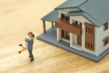 Couple Miniature 2 people standing model with house model make family Feel happy.as background real estate and family concept with copy space. Stok Fotoğraf