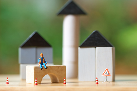 Miniature people Construction worker sitting on wood Investment Analysis Housing Or investment in movable property. using as background business concept and real estate concept with copy space for you