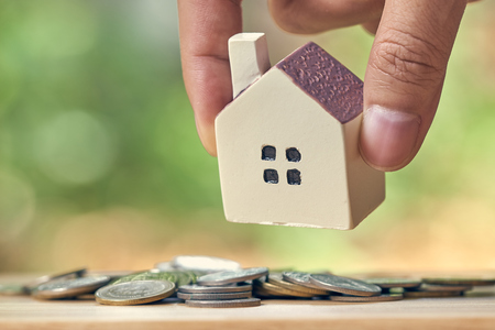 Businessman holding a model house model is placed on a pile of coins.using as background business concept and real estate concept with copy space for your text or design.