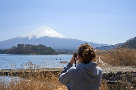 Young Asian tourists, aged 25-35, photographed with camera. Was photographed Mount Fuji. It is not a tourist destination in Japan. Stok Fotoğraf