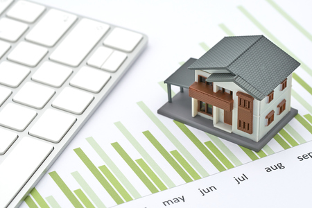 The house model is placed on the performance sheet, bar chart and keyboard. Long term investmentusing as background business concept and real estate concept with copy space for your text or design.