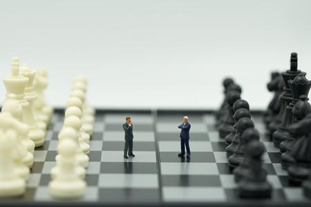 Miniature 2 people businessmen standing on a chessboard with a chess piece on the back Negotiating in business. as background business concept and strategy concept with copy space.