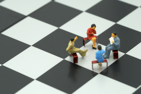 Miniature 4 people sitting on red staples placed on a a chessboard. meeting or Discussion using as background business concept with copy space and white space for your text or  design. Foto de archivo
