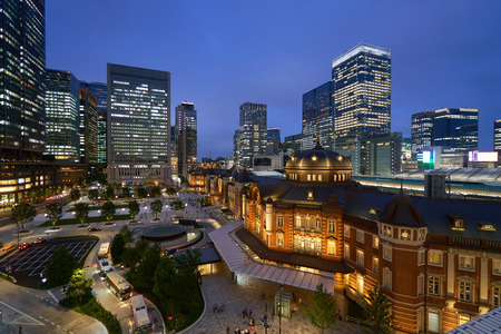 The night view of The Tokyo Station with the skyscrapers of marunouchi under a blue evening sky. Photoed in Tokyo, Japan. Stock Photo