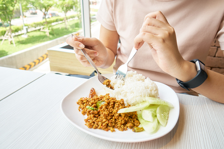 Asian girl eating lunch on the table. The food that is eaten in Thailand is called fried pork loin. Spicy and hot Fast food concept, healthy concept, Thai food, Asian food.