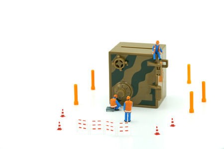 Miniature people Construction worker Security Key Repair And the treatment of the precious. on white background using as background business concept and Security concept with copy space.