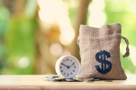 Money bags and watches put on the pile of money. as background business concept and Saving concept with  copy space for your text or design. Stock Photo