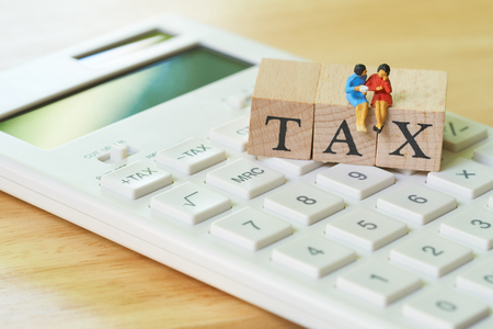 Miniature people Pay Annual income (TAX) for the year on calculator. using as background business concept and finance concept with copy space  for your text or  design.