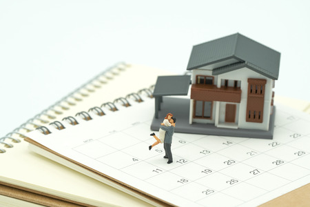 ouple Miniature 2 people standing on Calendar and A model house model is placed on a calendar and pen. as background property real estate concept with copy space for your text or  design.