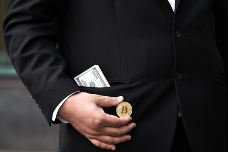 Businessman wearing a black suit holds a digital coin. It is popular among modern day investors. Suitable for investment.using as background business concept with copy space for your text or design.