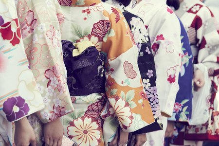 Young girls wearing Japanese kimono standing in front of the Temple in Tokyo, Japan. Kimono is a Japanese traditional garment.