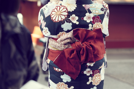 Young girl wearing Japanese kimono standing in front of the Temple in Tokyo, Japan. Kimono is a Japanese traditional garment.
